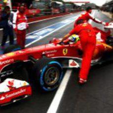 Los mecánicos de Ferrari entran el coche de Felipe Massa al box