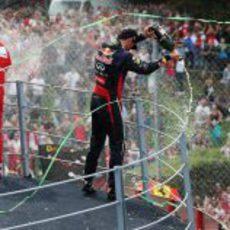 Mark Webber y Fernando Alonso echan champán a los aficionados