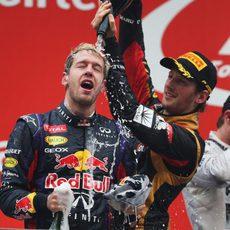 Romain Grosjean baña en champán a Sebastian Vettel
