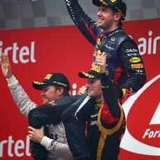 Nico Rosberg y Romain Grosjean aúpan a Sebastian Vettel