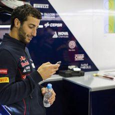 Daniel Ricciardo se entretiene con el móvil en el box de Toro Rosso en Brasil