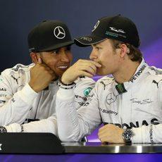 Lewis Hamilton y Nico Rosberg cuchichean en rueda de prensa