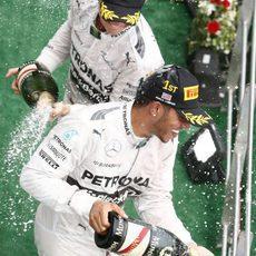 Lewis Hamilton y Nico Rosberg celebran con champán el doblete en Sepang