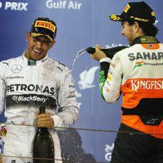 Lewis Hamilton recibe champán de Sergio Pérez