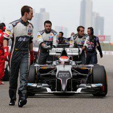 Adrian Sutil llevado por sus mecánicos hasta su posición de salida