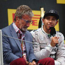 Eddie Jordan charla con Lewis Hamilton en el podio
