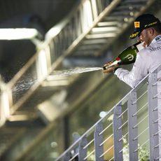 Lewis Hamilton lanza champán desde el podio