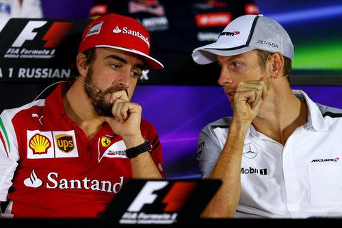 Fernando Alonso y Jenson Button comentan algo en rueda de prensa