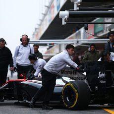 Los mecánicos llevan a Jenson Button de vuelta al box