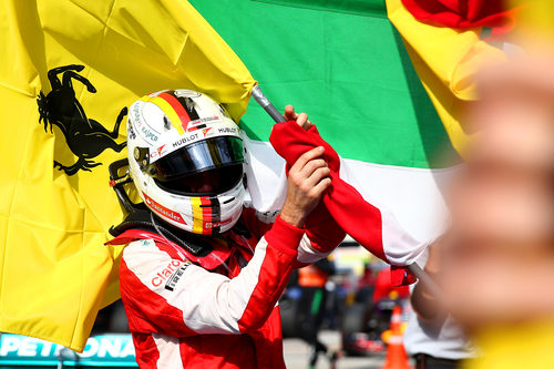 Sebastian Vettel coge la bandera de Ferrari para celebrar el triunfo