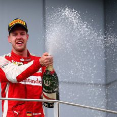 Sebastian Vettel moja con el champán a su equipo desde el podio