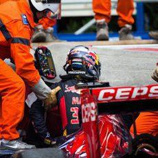 Los comisarios ayudan a salir del coche a Max Verstappen