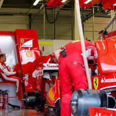 Sebastian Vettel en el box de Ferrari mientras el equipo trabaja