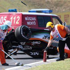 Los comisarios limpian la zona del accidente de Sergio Pérez