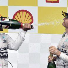 Lewis Hamilton moja a Nico Rosberg en la celebración de su victoria