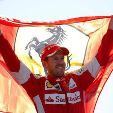 Sebastian Vettel sostiene la bandera de Ferrari