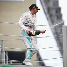 Lewis Hamilton lanza champán en el podio