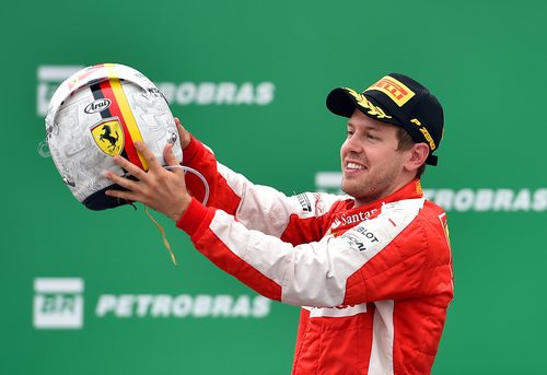 Sebastian Vettel sostiene su casco en el podio