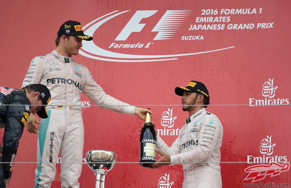 Nico Rosberg le pasa la botella a Lewis Hamilton