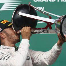 Lewis Hamilton bebe del trofeo ganador