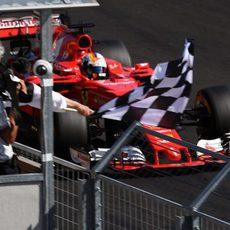 Vettel pasando junto a la bandera de cuadros