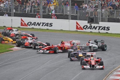 Fernando Alonso es tocado por Jenson Button en el primera curva