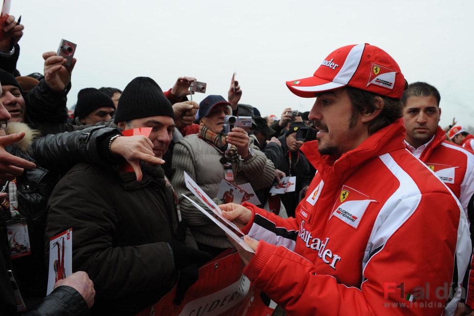 Alonso reparte fotos suyas firmadas