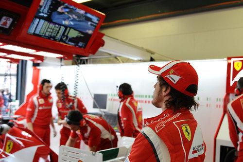 Alonso mira la sesión de clasificación desde su box