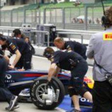 Un técnico de Pirelli vigila el RB7 de Webber