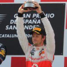 Button levanta su trofeo de tercer clasificado en el GP de España 2011