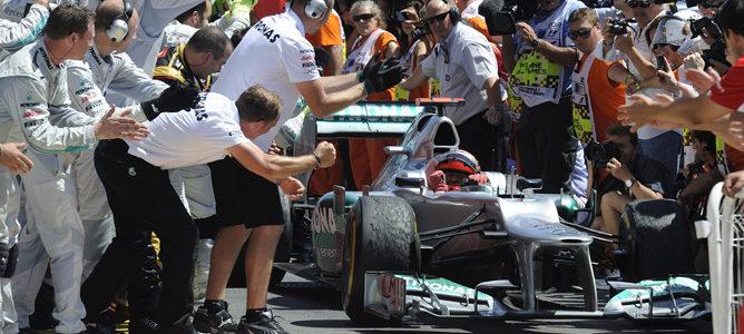 Michael Schumacher recibido por el equipo Mercedes tras lograr su podio en Valencia 2012