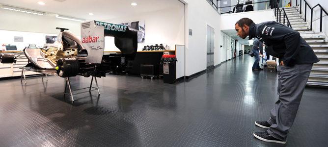 Lewis Hamilton observa un monoplaza de Mercedes en la fábrica de Brackley